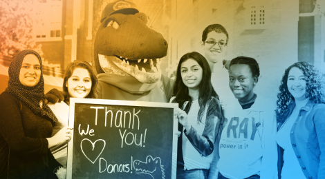 "students smiling with sign that says ""thank you donors"""